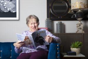 Elderly woman reading magazinr next to Sentai device