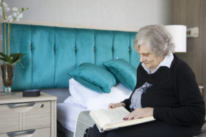 Elderly lady reading book and engaging with Sentai device