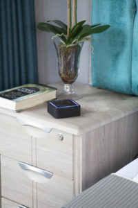 Sentai device sat on bedside table beside a book and vase of flowers